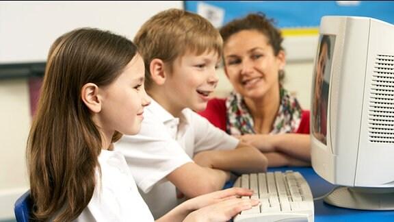 Symbolbild: IT-Unterricht an Schulen - Ein Mädchen und ein Junge werden von einer Lehrerin an einem Computer betreut.
