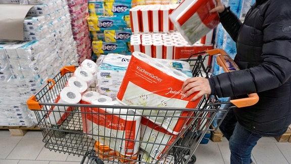 Hamsterkäufe wegen Corona-Virus, Frau kauft groߟe Mengen an Papiertüchern und Klopapier zur ܜberbrückung einer eventuellen Corona-Pandemie in Deutschland