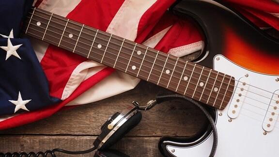 Alte gebrauchte Rockgitarre mit Kopfhörern und der amerikanischen Flagge