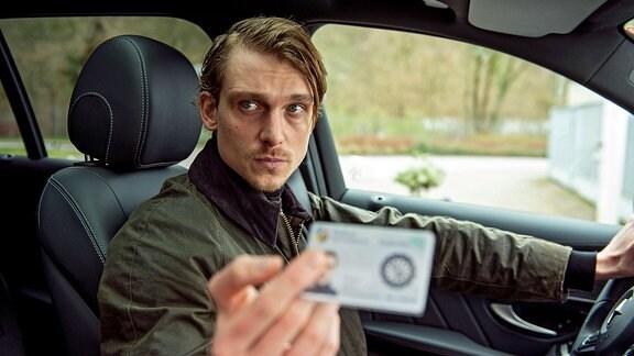 Filmszene - Hauptkommissar Adam Schürk (Daniel Sträßer) im Auto sitzend zeigt seinen Dienstausweis.