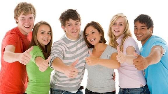 Junge Menschen stehen nebeneinander und zeigen ein Daumen hoch