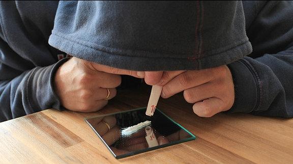 Ein Mann in Kapuzen-Shirt simuliert mit einem aufgerollten 10-Euro-Schein und weißem Pulver auf einem Spiegel das Konsumieren von Drogen