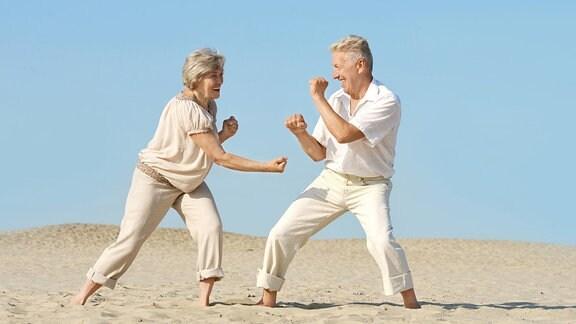 Ein älteres Ehepaar kampelt spaßhaft miteinander.