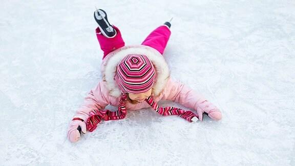 Ein Kind liegt auf einer Eisfläche.