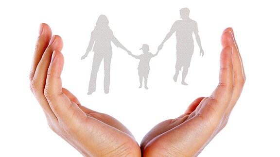 Schützende Hände schließen eine dreiköpfige Familie ein.