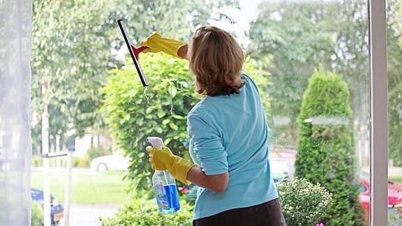 Eine Frau putzt mit einem Wischer ein Fenster
