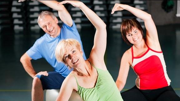 Drei Personen in einem Fitnessstudio machen auf Bällen sitzend Gymnastik