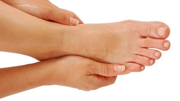 Eine Frau reibtsich die Füße ein.