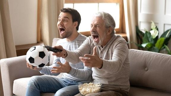 Zwei Männer sitzen mit Fußball und Fernbedienung in den Händen auf einem Sofa und jubeln