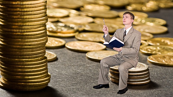 Ein Mann mit einem Notizbuch in der einen und einem Stift in der anderen Hand sitzt auf Münzen