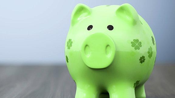 grünes Sparschwein mit vierblättrigen Kleeblättern