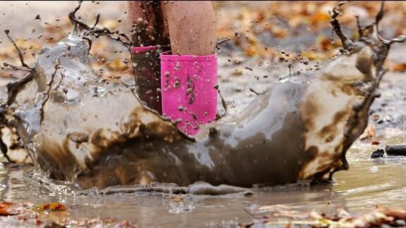 Ein Kind in rosa Gummistiefeln springt in eine Pfütze