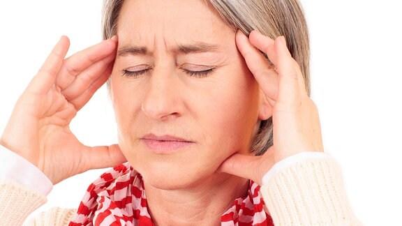 Eine Frau hält sich mit ihren Fingern den Kopf.