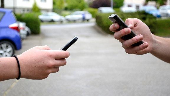 Zwei Hände halten jeweils ein Telefon