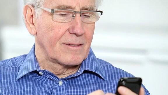 Ein älterer Mann mit einem Smartphone in der Hand.