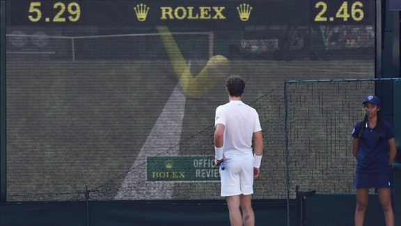 Tennisspieler schaut auf Bildschirm.