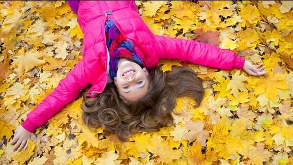 ein Mädchen liegt im Herbstlaub und lacht.
