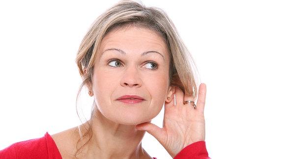 Frau mittleren Alters hält ihre Hand hinter ein Ohr