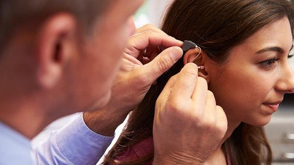 Eine Hör-Akustiker passt ein Hörgerät an.