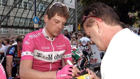 Jan Ullrich (Deutschland/T Mobile) schreibt ein Autogramm auf eine Wasserflasche der Tour de France.