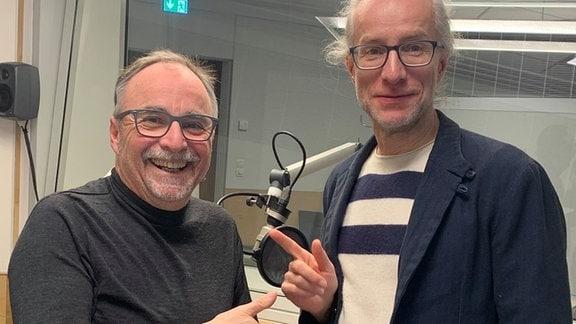 Zwei Männer stehen in einem Aufnahmestudio nebeneinander