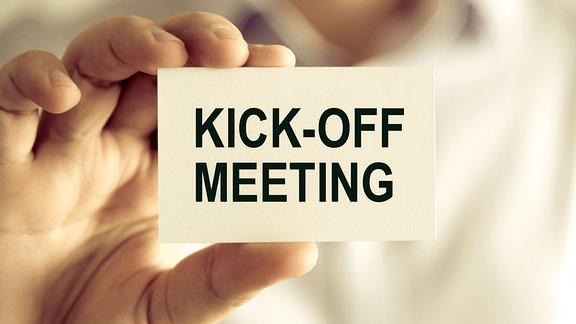 Nahaufnahme auf die Hand eines Geschäftsmann, der eine Karte mit Text hält auf der ''Kick-off Meeting'' steht.