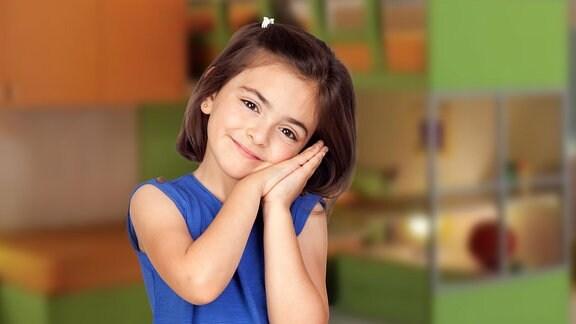 Lächelndes Mädchen hält Kopf seitlich geneigt und auf die gefalteten Hände gelegt.