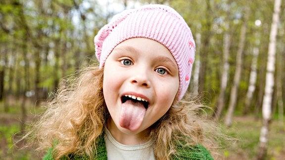 Ein im Wald stehendes fröhliches Mädchen streckt frech die Zunge heraus.
