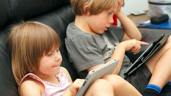 Zwei Kinder im Vorschulalter spielen auf einer Couch sitzend mit ihren Tabletts
