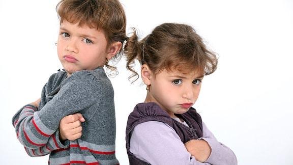 Zwei Mädchen stehen Rücken an Rücken und schauen zornig