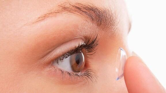 Junge Frau setzt sich Kontaktlinse ein.