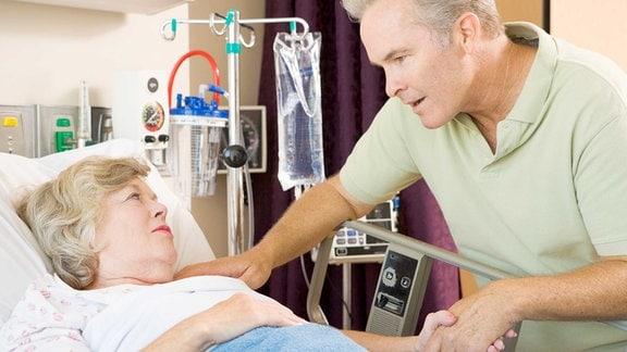 Eine Frau liegt im Krankenbett und spricht mit einem Mann, der daneben steht.