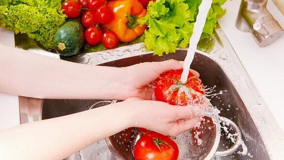 Tomate wird über einem Sieb in einen Wasserstrahl gehalten