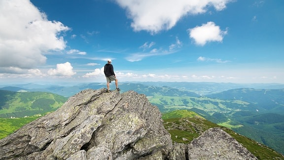 Ein Mann steht auf einem Berggipfel