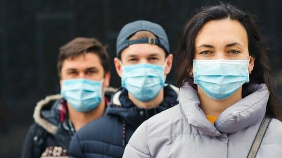 Drei Personen mit Mund-Nasen-Schutz