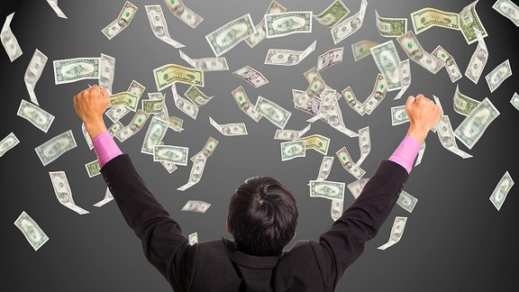 Geschäftsmann greift mit seinen Händen nach Geldscheinen welche in der Luft herumwirbeln.