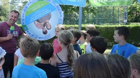 Ein Mann mit Mikrofon in der Hand steht neben einem Glückrad, auf dem zwei Personen zu erkenen sind. Vor ihm steht eine Gruppe von Kindern.