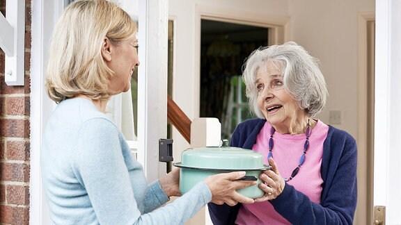 Eine Frau überreicht einer anderen einen Topf an der Haustür.