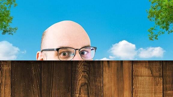 Mann schaut über einen Zaun.