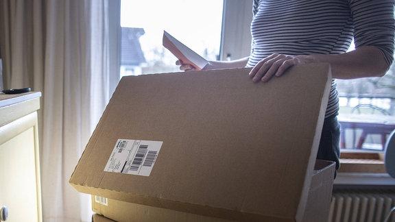 eine Frau packt ein Paket aus