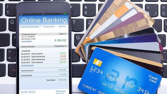 Ein Smartphone mit Onlinebanking App und Kreditkarten.