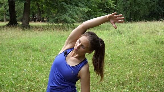 Eine junge Trainerin zeigt Fitnessübungen.