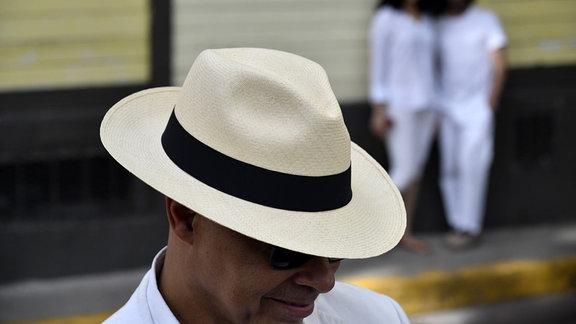 Ein Mann trägt einen Panama-Hut