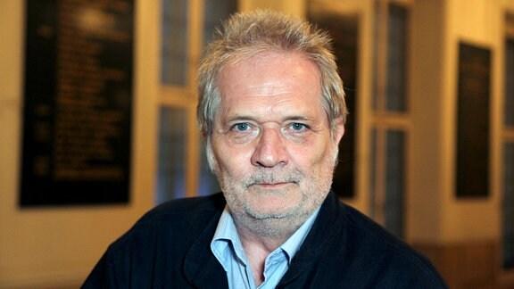 Peter Eötvös, Komponist. Ein Mann mit kurzem grauen Haar und Bart, sitzt im Wiener Opernhaus und schaut freundlich in die Kamera.