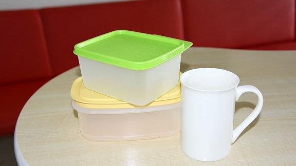 Plastedosen mit bunten Deckeln und eine Kaffeetasse stehen auf einem Tisch.