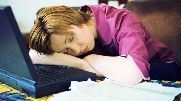 Frau liegt schlafend auf einem Tisch vor einem Laptop