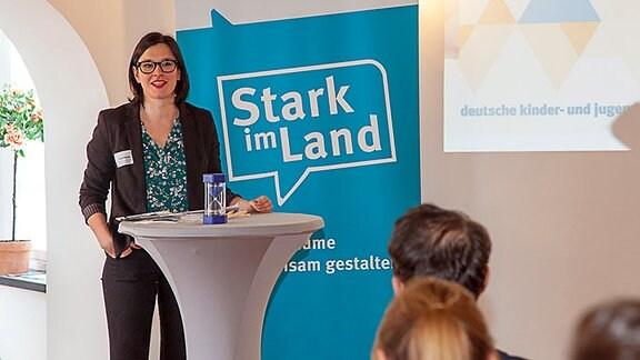 Eine junge, dunkelhaarige Frau mit Brille (Aniko Popella) steht an einem Rednerpult