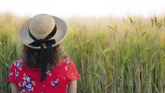 Rückansicht einer Frau, die einen Strohhut und ein rotes Sommerkleid trägt und vor einem Feld steht.