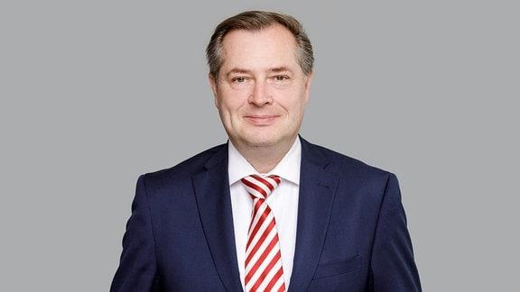 Ein Mann mit kurzen graubrauen Haaren
