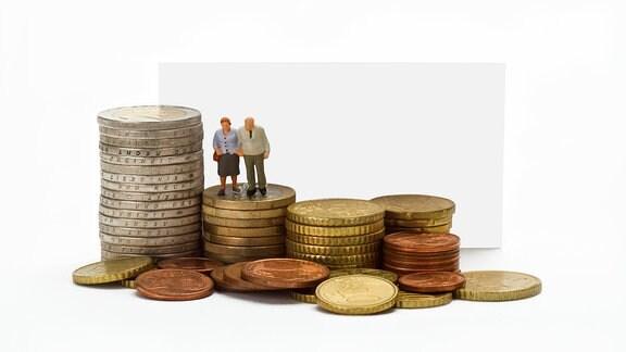 Figuren eines Rentnerpaares stehen auf Münzstapeln